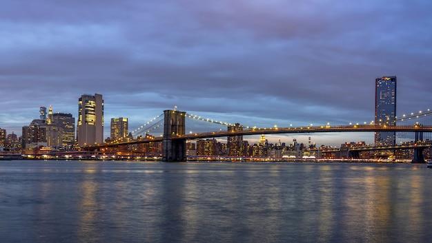 Scène panoramique du pont de brooklyn au bord de la rivière est avec le paysage urbain de new york au crépuscule Photo Premium