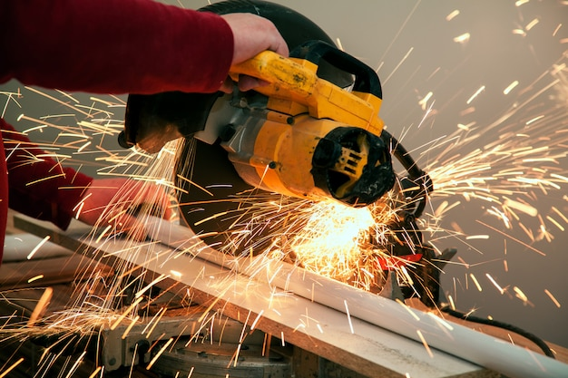 Sciage ouvrier coupant et soudant du métal avec de nombreuses étincelles tranchantes Photo Premium