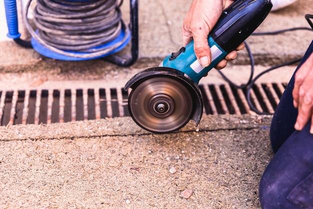 Scie radiale actionnée par un opérateur, sur un chantier de construction. Photo Premium