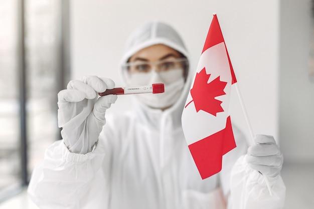 Le Scientifique En Combinaison Avec Un échantillon De Coronavirus Et Le Drapeau Canadien Photo gratuit