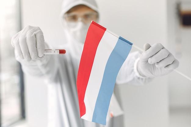 Le Scientifique En Combinaison Avec Un échantillon De Coronavirus Et Le Drapeau Des Pays-bas Photo gratuit