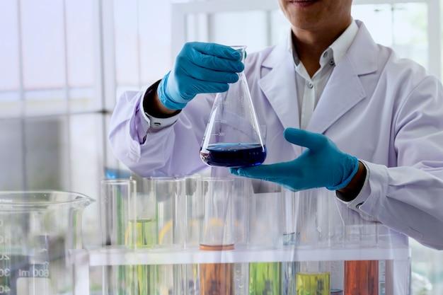Un scientifique examine une fiole d'erlenmeyer pour observer la réaction chimique dans un laboratoire de chimie. Photo Premium
