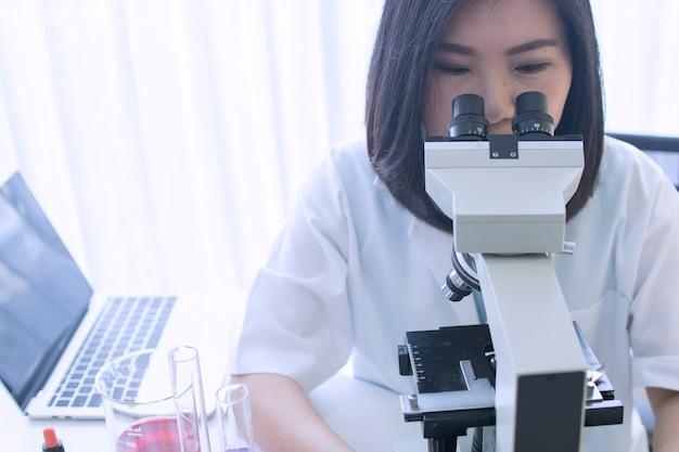 Scientifique expérimenter un liquide chimique en regardant au microscope Photo Premium