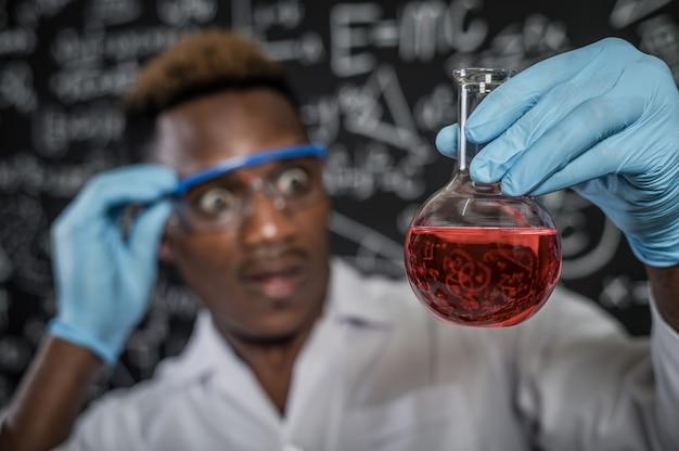 Des scientifiques choqués par les produits chimiques rouges dans le verre du laboratoire Photo gratuit