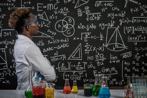 Les scientifiques portent des lunettes et croisent les bras pour voir la formule en laboratoire Photo gratuit