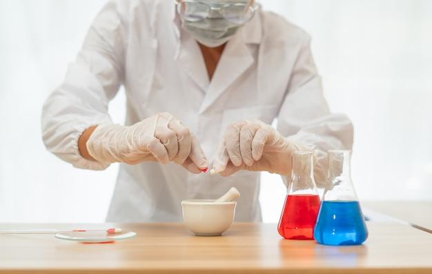 Les Scientifiques Versent Des Médicaments à Partir De Capsules Dans Une Tasse De Broyage De Médicaments Sur Fond D'isolat Blanc, Photo Premium