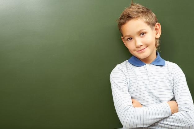 Scoolboy debout en classe près du tableau noir Photo gratuit