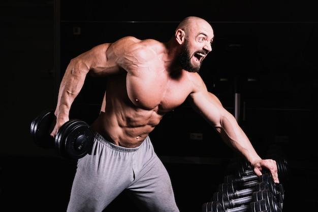 Screaming homme soulevant haltères lourds Photo gratuit