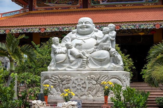 Sculpture En Marbre De L'heureux Bouddha Avec Des Enfants Dans Un Temple Bouddhiste De La Ville De Danang Photo Premium