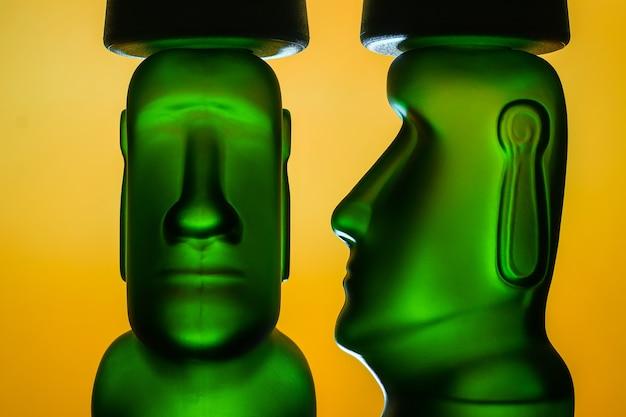 Sculpture De Moai Humanoïde De Couleur Verte Et Jaune Isolée Sur Fond Orange Photo Premium