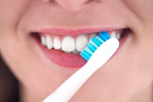 Se Brosser Les Dents Avec Un Gros Plan De Brosse à Dents électrique à Ultrasons. Hygiène Dentaire Et Soins Dentaires Photo Premium