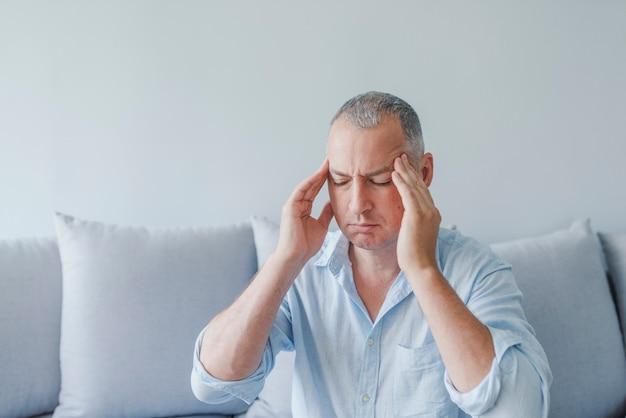 Se sentir stressé. frustré beau jeune homme se touchant la tête et gardant les yeux fermés Photo Premium