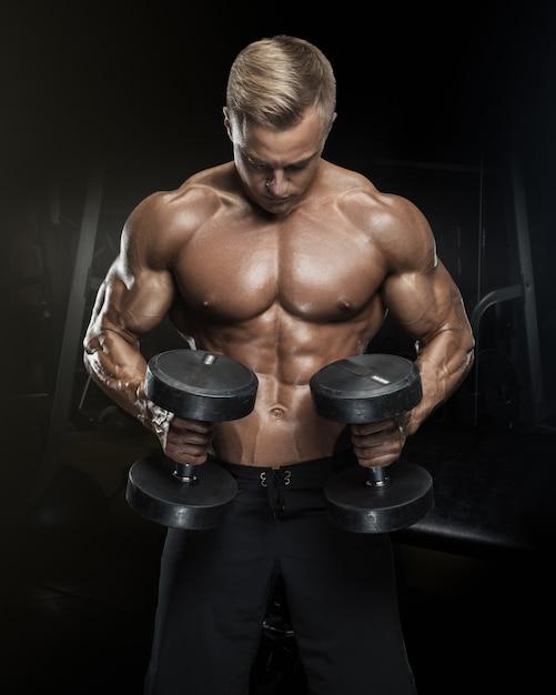Séance D'entraînement De Beau Mec Athlétique Avec Des Haltères Photo Premium