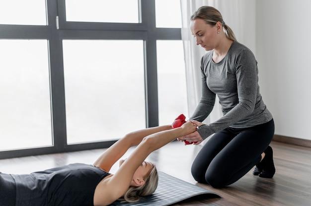 Séance D'entraînement Avec Un Entraîneur Personnel Portant Sur Un Tapis De Yoga Photo gratuit