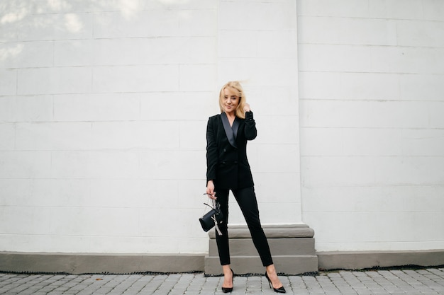 Séance photo de mode rue de la jeune femme élégante dans un vêtement gris Photo gratuit