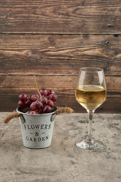 Seau En Métal De Raisins Frais Rouges Et Verre De Vin Blanc Sur Une Surface En Marbre. Photo gratuit