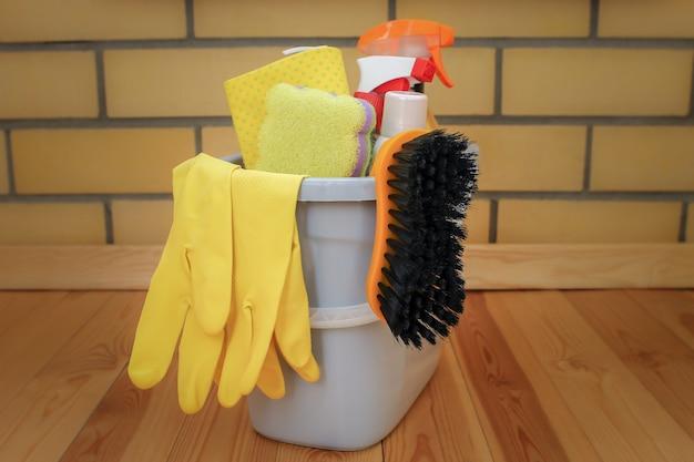 Seau avec des produits de nettoyage sur un plancher en bois. lavez et des gants avec une éponge dans un seau en plastique Photo Premium
