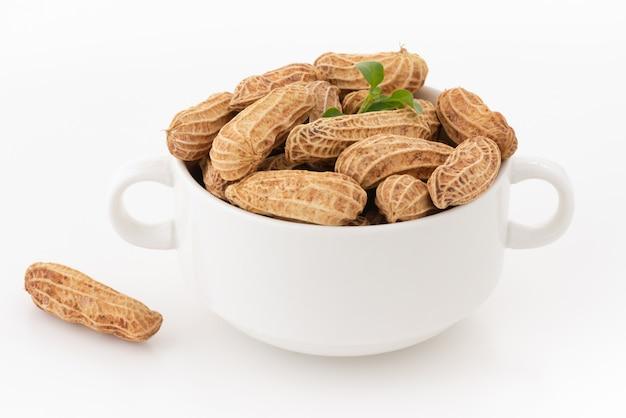 Sécher les cacahuètes dans un bol blanc sur blanc isolé Photo Premium
