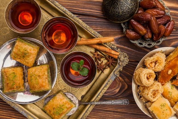 Sécher les dattes sur la soucoupe près des tasses de thé et des desserts turcs sur le plateau Photo gratuit