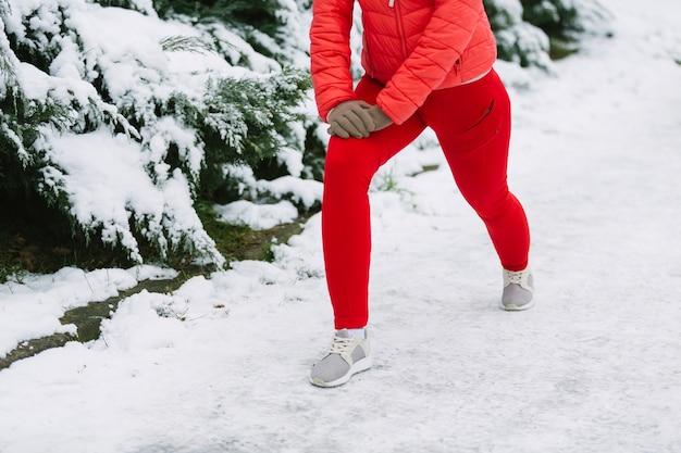 Section basse d'athlète féminine s'exerçant sur la neige Photo gratuit