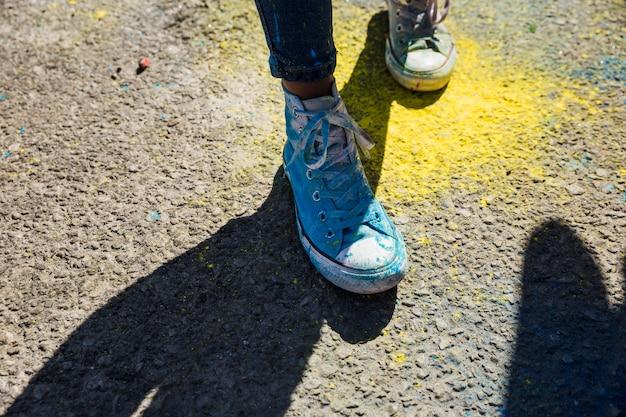 Section basse de chaussures de femme avec poudre de couleur holi Photo gratuit