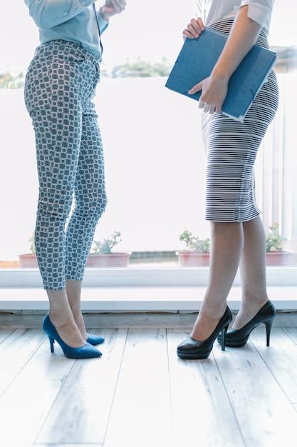 Section basse de deux femmes d'affaires debout près de l'entrée Photo gratuit
