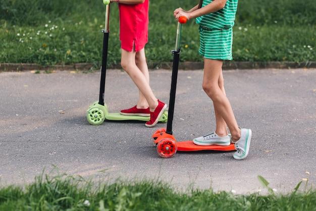 Section basse, deux, filles, équitation, coup pied, scooter, dans parc Photo gratuit