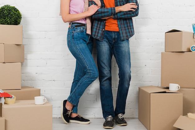 Section basse du couple debout entre les boîtes en carton avec deux tasses Photo gratuit