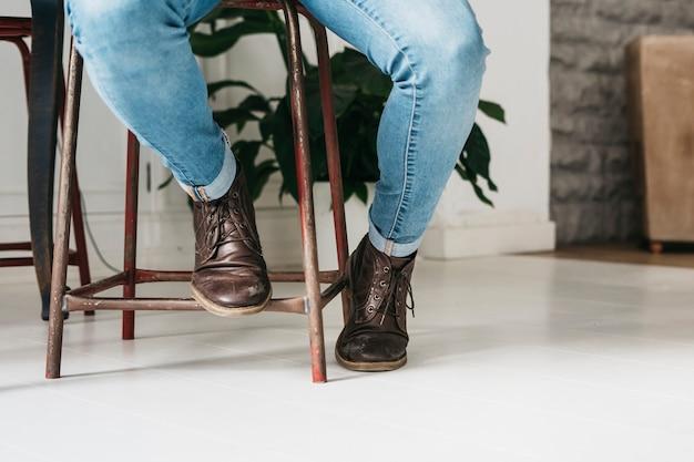 Section basse d'élégant homme élégant en chaussures marron assis sur un tabouret Photo gratuit