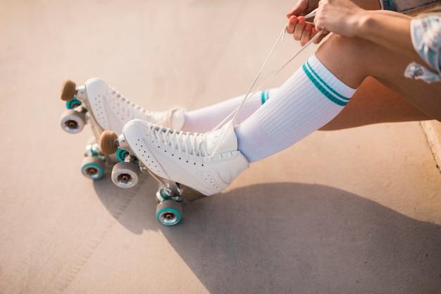 Section basse de la femme attachant de la dentelle de patin à roulettes Photo gratuit