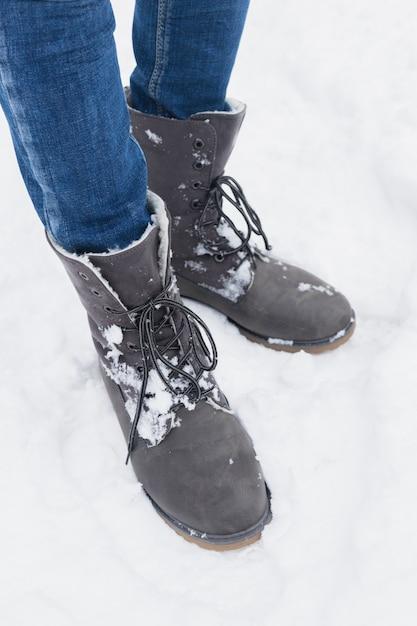 Section Basse De La Femme Debout Avec Des Bottes D'hiver Dans La Neige Photo gratuit