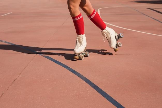 Section basse d'une femme patinant sur un terrain extérieur Photo gratuit