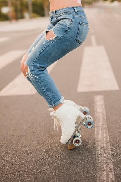 Section basse d'une femme portant des patins à roulettes blanches en équilibre sur la route Photo gratuit