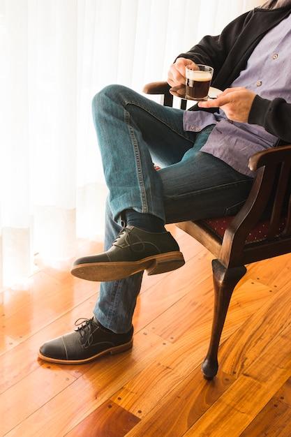 Section basse d'un homme assis sur une chaise tenant une tasse de café à la main Photo gratuit