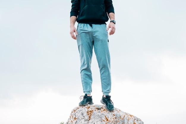 Section basse, de, a, homme, debout, sur, rocher, contre, ciel bleu Photo gratuit