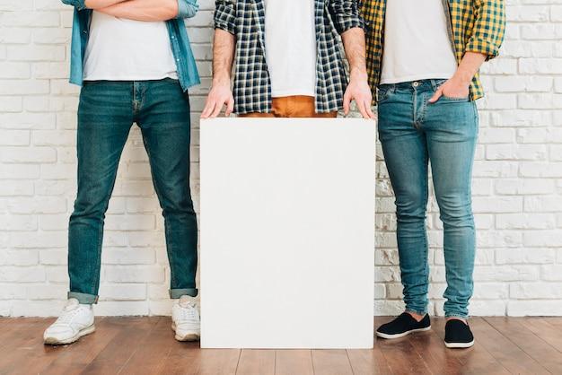 Section basse d'un homme montrant une pancarte blanche avec leurs amis Photo gratuit