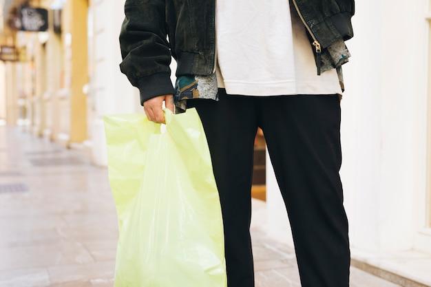 Section basse d'un homme portant un sac en plastique à la main Photo gratuit