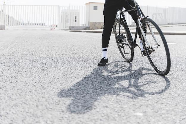 Section basse d'un homme à vélo debout sur la route Photo gratuit