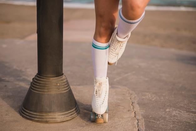 Section basse d'une patineuse debout sur une jambe près du pilier Photo gratuit