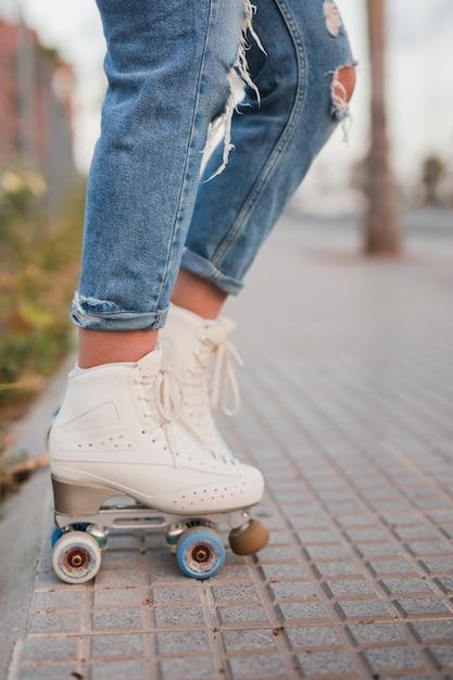 Section basse d'une patineuse en patins à roulettes blanches se tenant sur le trottoir Photo gratuit