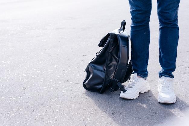 Section basse d'une personne debout dans la rue avec un sac à dos noir Photo gratuit