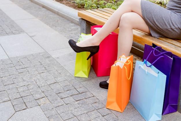 Section basse vue d'une jambe de femme avec des sacs à provisions multicolores Photo gratuit