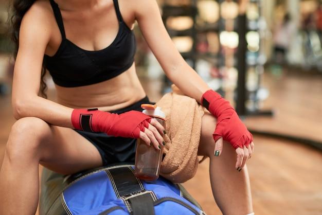 Section médiane d'un boxeur méconnaissable prenant du repos après l'entraînement Photo gratuit