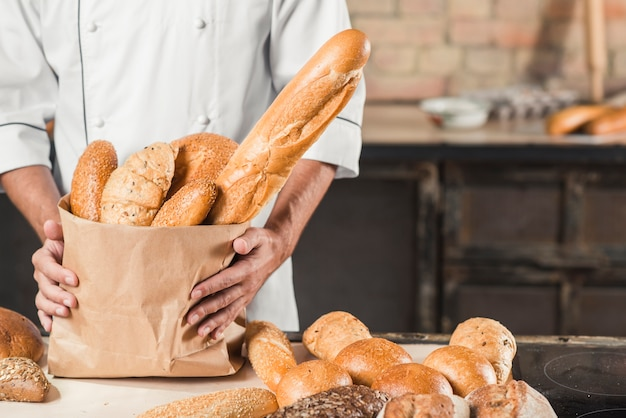 Section médiane du boulanger mâle tenant un sac en papier avec différents types de pains Photo gratuit