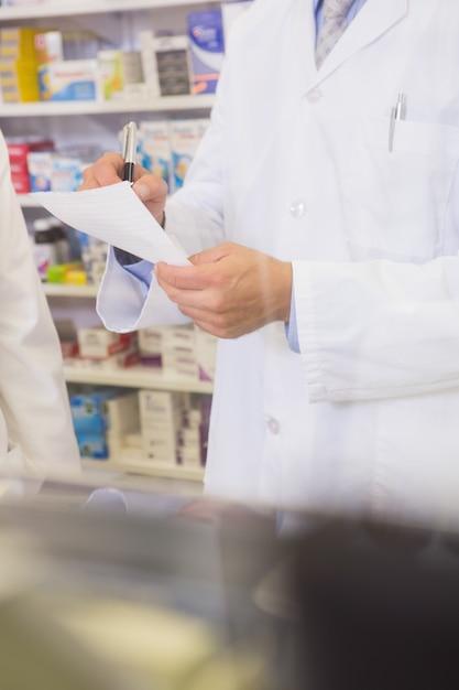 Section médiane du pharmacien rédigeant une ordonnance Photo Premium