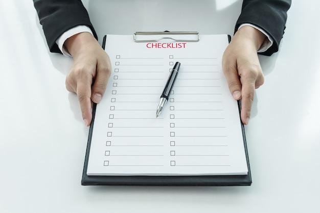 Section médiane de la femme d'affaires détenant presse-papiers avec liste de contrôle contre Photo Premium