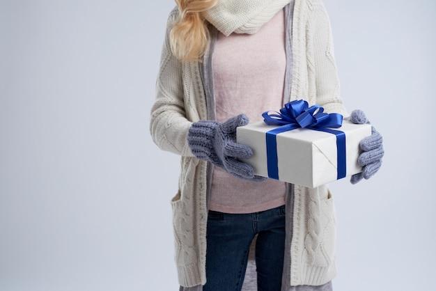 Section médiane d'une femme anonyme tenant le cadeau du nouvel an Photo gratuit