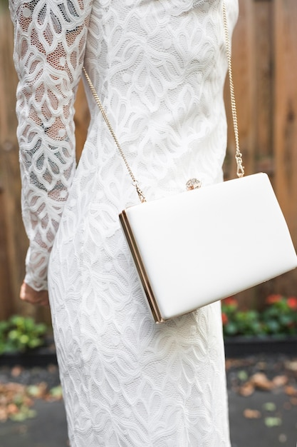 Section médiane d'une femme en robe blanche avec pochette Photo gratuit