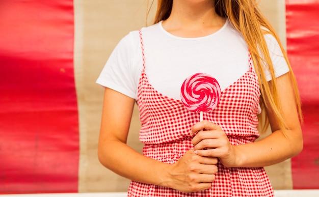 Section médiane d'une femme tenant une sucette à la main Photo gratuit