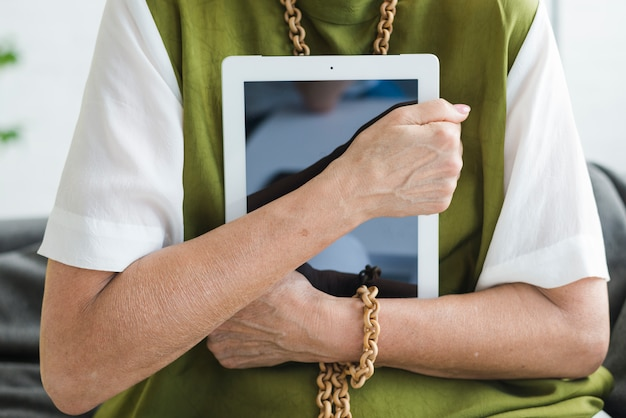 Section médiane de la femme tenant une tablette numérique Photo gratuit